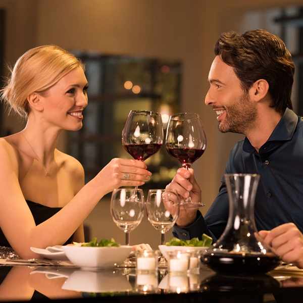 Dressed couples smile and clink of glass on glass in restaurant with plates and appetizers on table.
