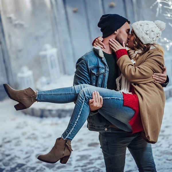 A guy picking a girl up and kissing her with care and affection against the background in the snow