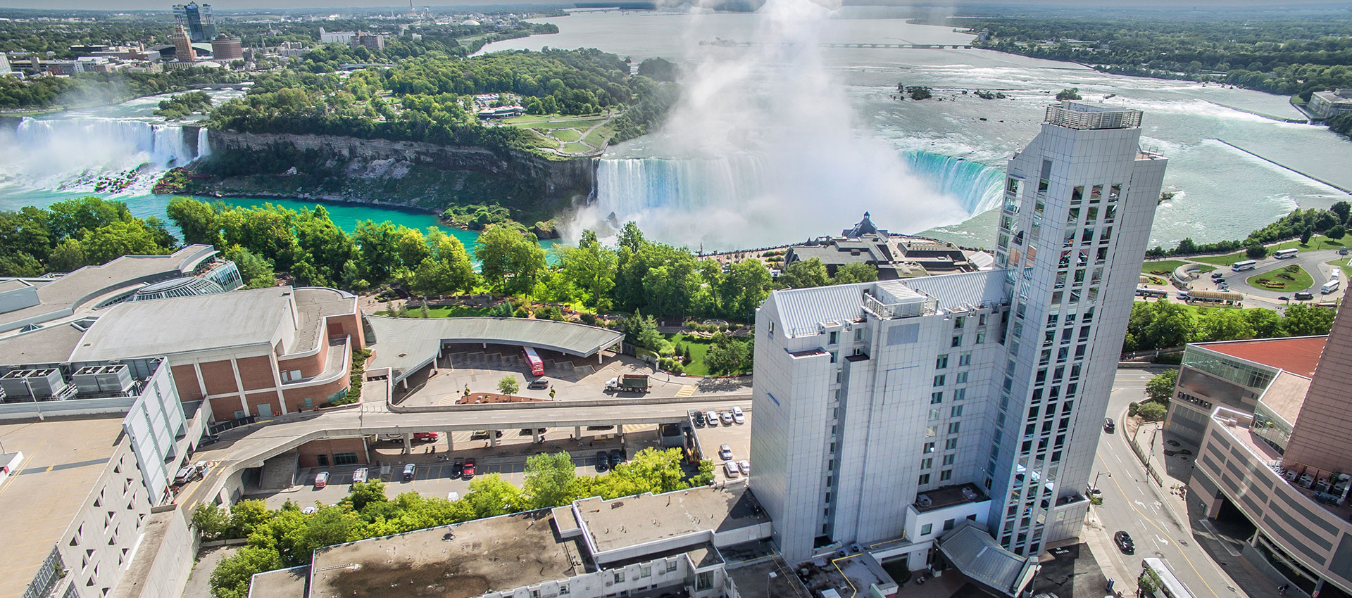 an overlook of the Oakes Hotel and the Niagara Falls next to it from view on the sky on a sunny day