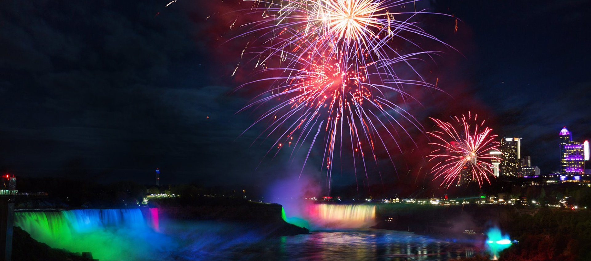 Exploding fireworks illuminate the sky on the Niagara Falls with shimmering light at night